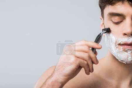 Photo for Handsome young man foam on face shaving with razor, isolated on grey - Royalty Free Image