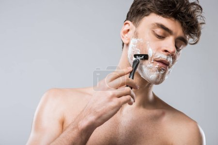 Photo for Handsome caucasian man foam on face shaving with razor, isolated on grey - Royalty Free Image