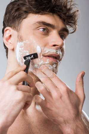 Photo for Handsome man foam on face shaving with razor, isolated on grey - Royalty Free Image