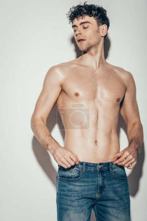 Photo for Sexy shirtless stylish man in jeans posing on grey - Royalty Free Image