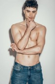 sexy shirtless fashionable man in jeans posing on grey