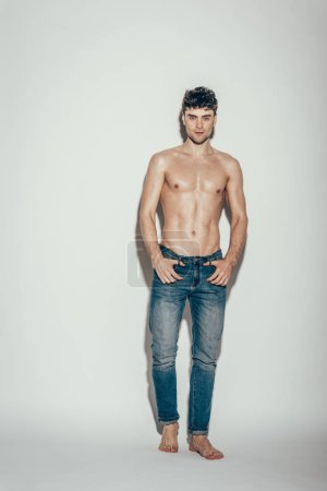 Photo for Sexy fashionable man in jeans posing on grey - Royalty Free Image