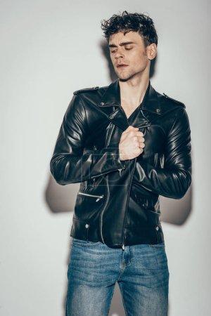 Photo pour Bel homme sexy posant en veste en cuir noir sur gris - image libre de droit