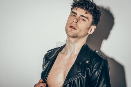 Photo for Handsome sexy shirtless man posing in black leather jacket on grey - Royalty Free Image