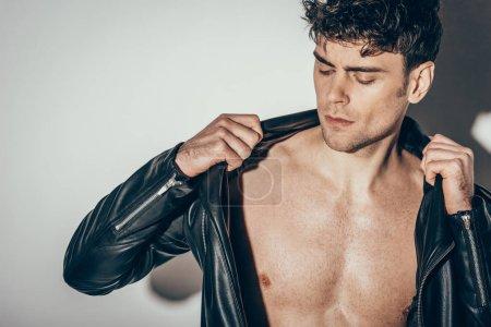 Photo pour Beau jeune homme torse nu portant une veste en cuir noir sur gris - image libre de droit