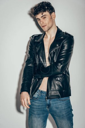 Foto de Con estilo hombre sexy posando en vaqueros y chaqueta de cuero negro sobre gris - Imagen libre de derechos