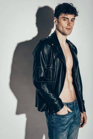 handsome stylish man posing in black leather jacket on grey