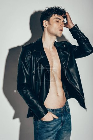 Photo for Handsome sexy man posing in jeans and black leather jacket on grey - Royalty Free Image