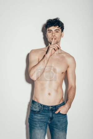 Photo for Sexy shirtless man in jeans showing silence symbol while posing on grey - Royalty Free Image