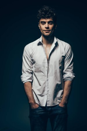 stylish handsome man posing in white shirt isolated on dark grey