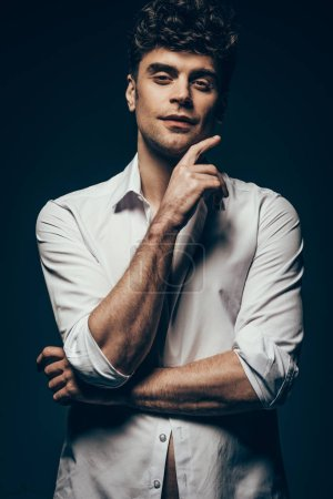 stylish sexy man posing in white shirt isolated on dark grey