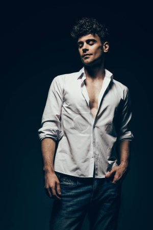 fashionable handsome man posing in white shirt isolated on dark grey