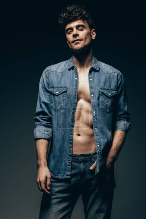 handsome muscular man posing in denim shirt isolated on grey