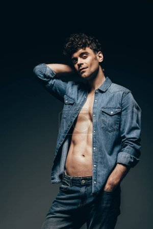 sexy macho posing in denim clothes isolated on dark grey