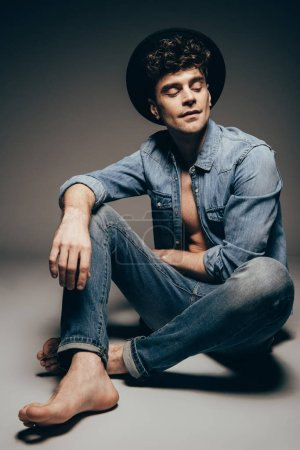 Photo for Stylish young man posing in jeans clothes and hat on dark grey - Royalty Free Image