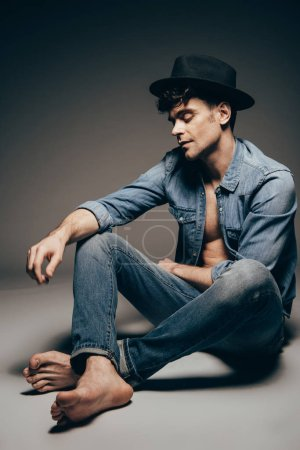 Photo for Handsome sexy man posing in denim clothes and trendy hat on dark grey - Royalty Free Image
