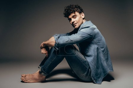 sexy barefoot man sitting in jeans clothes on dark grey