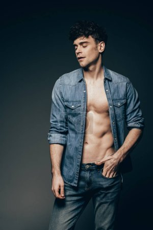 handsome sexy man posing in jeans clothes isolated on dark grey