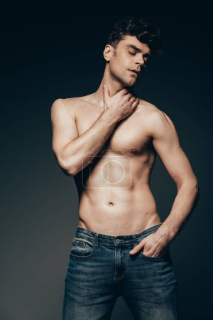 sexy shirtless man in jeans posing isolated on dark grey