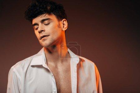 Photo pour Bel homme rêveur qui pose en chemise blanche, isolé sur brown - image libre de droit