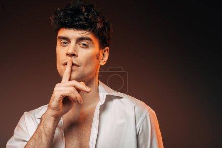 Photo pour Bel homme en chemise blanche montrant le symbole du silence, isolé sur brun - image libre de droit