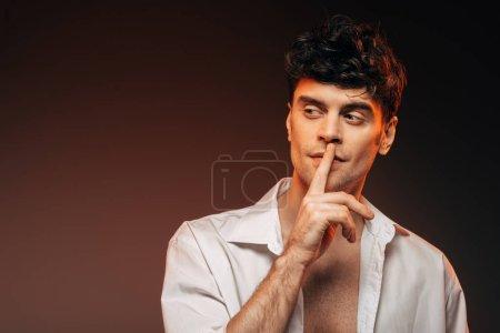Photo pour La mode homme en chemise blanche montrer signe de hush, isolé sur brown - image libre de droit