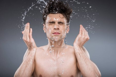handsome man splashing water into face, isolated on grey