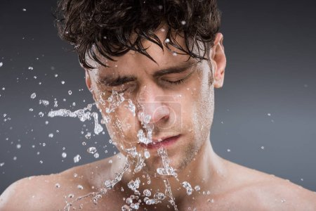 Photo for Handsome man washing face with water in the morning, isolated on grey - Royalty Free Image