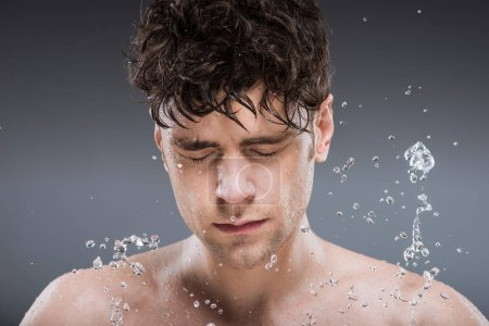 young man washing face with water, isolated on grey
