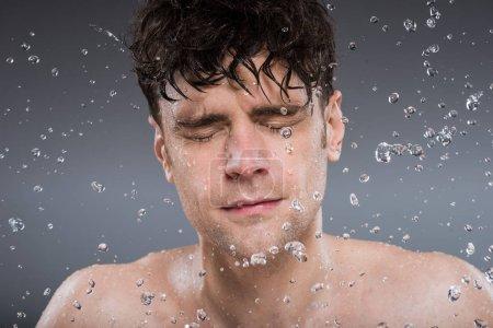 bel homme qui lave le visage avec de l'eau, isolé sur gris
