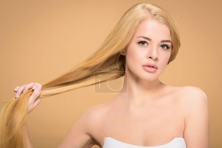 Photo for Pretty girl holding long straight hair on beige background - Royalty Free Image