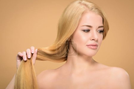Naked blonde woman touching straight hair and looking away