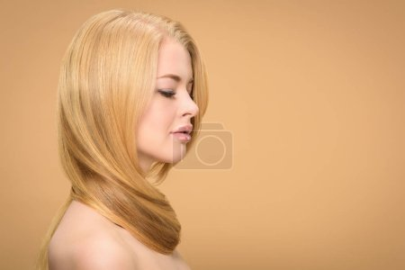 Photo for Side view of sensual woman with long hair around neck on beige background - Royalty Free Image