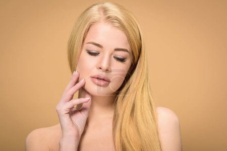 Relaxed blonde woman touching face with eyes closed