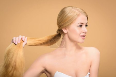 Photo for Beautiful young blonde woman holding long hair and looking away isolated on beige - Royalty Free Image