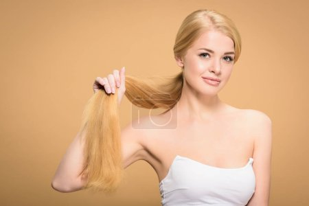 Foto de Hermosa joven rubia sosteniendo el pelo largo y sonrisa en cámara aislada en beige - Imagen libre de derechos