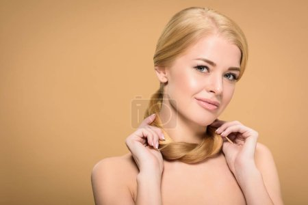 Photo for Attractive naked woman holding long blonde hair around neck and smiling at camera isolated on beige - Royalty Free Image