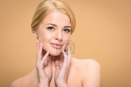 Photo for Attractive naked blonde girl touching face with hands and smiling at camera isolated on beige - Royalty Free Image