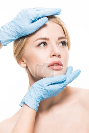 Photo for Cropped shot of cosmetologist in medical gloves touching face of beautiful woman isolated on white - Royalty Free Image