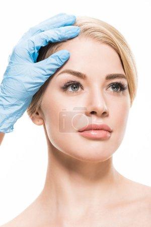 Photo pour Plan recadré de cosmétologue en gant de latex touchant le front de belle femme isolée sur blanc - image libre de droit