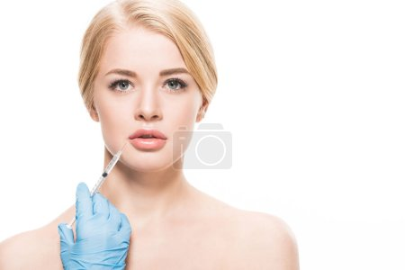 Photo for Beautiful naked woman receiving beauty injection in lips and looking at camera isolated on white - Royalty Free Image