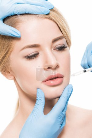 Foto de Cropped shot of cosmetologists making beauty injection to young woman isolated on white - Imagen libre de derechos
