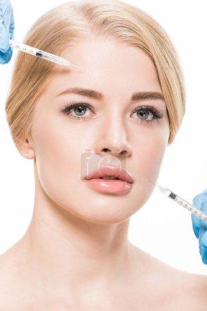 Foto de Bella mujer recibiendo inyecciones de belleza en rostro aislado en blanco - Imagen libre de derechos