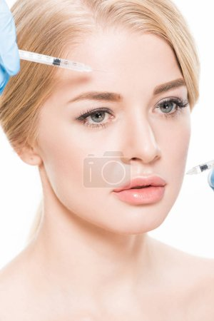 Photo pour Cropped shot of cosmetologist making beauty injections to attractive young woman isolated on white - image libre de droit