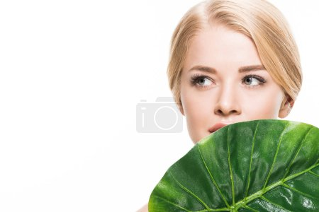 Photo for Beautiful tender young woman with green tropical leaf looking away isolated on white - Royalty Free Image