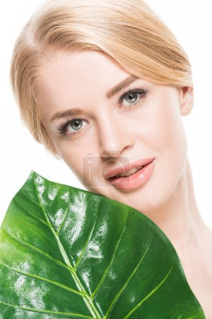 Photo pour Belle femme blonde tenant vert feuille tropique et souriant à la caméra isolé sur blanc - image libre de droit