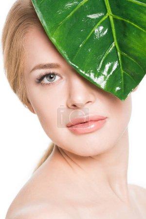 attraktive nackte Mädchen mit grünem Blatt nahe Auge Blick auf Kamera isoliert auf weiß