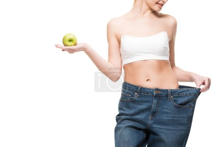 cropped shot of smiling slim woman in oversized jeans holding green apple isolated on white