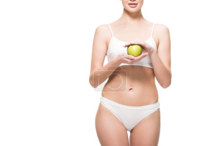 Photo for Cropped shot of slim young woman in underwear holding fresh green apple isolated on white - Royalty Free Image