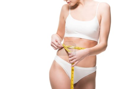 cropped shot of young woman in underwear measuring waist with tape isolated on white
